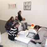 Besucher der Ausstellung sehen sich Kataloge an
